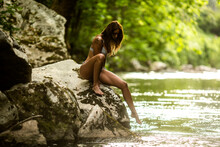 Side View Of Alluring Young Fit Female Traveler In Bikini Sitting On Rocky Cliff Near Lake In Green Lush Rainforest In Fuente De