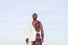 Determined African American Male Model In Traditional Costume Standing On Background Of Blue Cloudy Sky And Looking At Camera