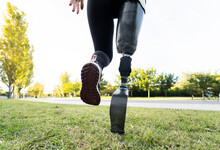Back View Of Crop Anonymous Female Runner With Leg Prosthesis Exercising In Park During Active Workout