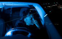 Through Windshield View Of Upset Young Female Driver Crying About Personal Problems While Sitting In Car Parked On Night Road