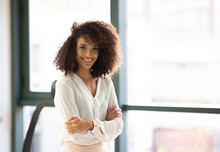 Cheerful Young Curly Haired Ethnic Female In Casual Outfit Standing Near Window And Looking At Camera While Having Break During Work In Modern Workspace