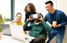 Unrecognizable Black Man With VR Headset Exploring Virtual World While Sitting At Table With Laptop Surrounded By Cheerful Multiracial Colleagues In Modern Workplace