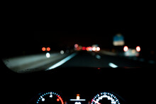 Blurred Illuminated Dashboard And View From Windshield Of Car Driving Along Asphalt Highway At Night