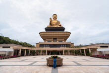 Back View Of Unrecognizable Female Traveler Standing On Staircase In Front Of Fo Guang Shan Buddha Museum With Huge Buddha Statue On Roof In Kaohsiung City In Taiwan