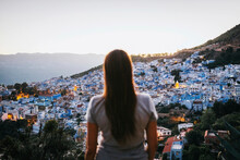 Back View Of Unrecognizable Young Female Tourist Admiring Picturesque Cityscape With Cozy Typical White And Blue Houses Located On Hill Slope Against Sunset Sky In Chefchaouen