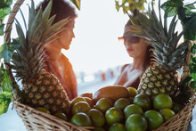 Side View Of Blurred Ethnic Couple Talking Friendly While Standing Near Wicker Basket Full Of Fresh Tropical Fruits In Beach Bar In Summer Day