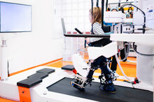 Full Body Side View Of Disabled Little Girl Exercising On Special Treadmill During Physiotherapy Session In Modern Equipped Rehabilitation Center