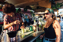 African American Barman Making Refreshing Alcoholic Cocktail With Ice And Lime For Female Client In Outdoor Bar In Summer Evening