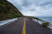 Empty Asphalt Roadway With Yellow Marking Lines Running Between Green Hill And Sea Water Under Gray Cloudy Sky