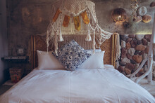 Comfortable Bed With White Linen And Ornamental Cushion In Hotel Room With Natural Stone Walls And Hanging Rope Decoration In Taiwan