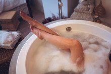 From Above Of Relaxed Young Asian Female Sitting In Small Round Bathtub With Foam And Enjoying Bath Procedure In Spa Salon With Oriental Decor