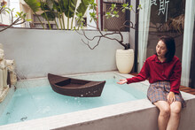 Calm Young Asian Female Enjoying Crystal Clear Water Of Fountain With Small Boat In Pool And Stone Sculptures While Resting In Tropical Hotel In Taiwan