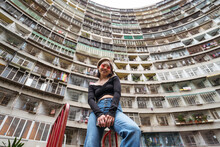 From Below Of Young Female In Casual Outfit Standing Against Multistory Residential Building With Geometric Curved Walls On Street Of Kaohsiung City In Taiwan