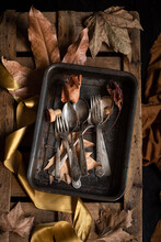 Top View Of Retro Metal Spoons And Forks Placed On Rustic Wooden Palette With Dried Autumn Leaves