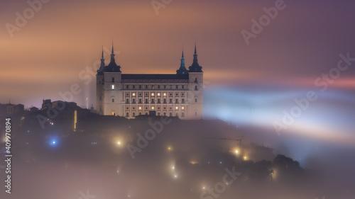 Amazing scenery of shining and luminous ancient Alcazar de Toledo castle over town in misty twilight
