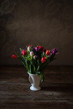 High Angle Of Bouquet Of Fresh Colorful Tulips In Ceramic Vase Placed On Wooden Table At Home