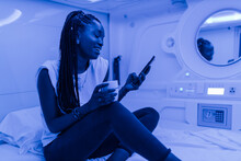 Cheerful Black Female Sitting With Cup Of Drink On Bed In Room Of Capsule Hotel And Texting Message On Smartphone While Resting During Vacation