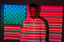 Serious African American Male Illuminated By Red And Blue Neon Projection Of National American Flag Standing In Dark Studio