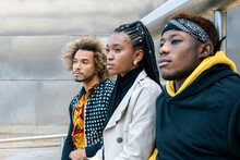 Serious Unemotional Young African American Friends In Casual Informal Clothes Standing On Stairway Looking Away While Spending Time Together In City