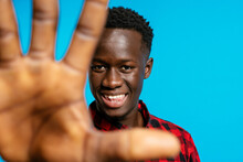 Positive Handsome African American Male In Red Checkered Shirt Standing On Vibrant Blue Background In Studio And Reaching Hand Towards Camera