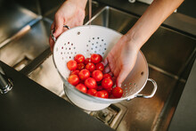 From Above Of Crop Unrecognizable Female Washing Pile Of Ripe Cherry Tomatoes In Metal Colander In Kitchen