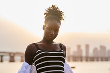 Tranquil Pensive Young African American Female In Casual Clothes Looking At Camera And Relaxing On Urban Seafront At Sunset Time