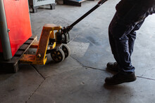 Side View Of Crop Anonymous Workman Pulling Trolley With Heavy Metal Equipment While Working In Professional Service Workshop