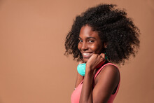 Laughing Young Cuban Woman With Afro Hairstyle Wearing Colorful Dress And Headphones Standing In Studio