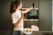 Side View Of Female Blogger Standing In Kitchen With Bowl Of Fresh Vegetable Salad And Taking Selfie On Smartphone