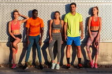 Group Of Multiethnic Fit Runners In Sportswear Leaning On Wall Of Building While Standing On Street On Sunny Day