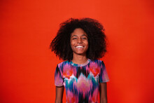 Modern Cuban Woman With Afro Hair Wearing Bright Dress And Smiling At Camera Against Red Studio Background