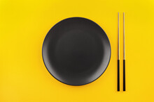 Mockup Empty Black Round Plate With Gilded Chinese Chopsticks Flat Lay On Yellow Background With Copy Space