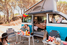 Company Of Friendly Women Relaxing Together Near Camper Van And Having Picnic In Summer On Sunny Day