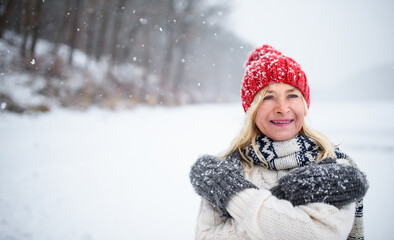 Front view portrait of senior woman with hat and mittens outdoors standing in snowy nature.