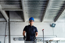 Low Angle Of Cheerful Male Worker In Hardhat And Protective Glasses Standing On Ladder And Installing Metal Pipe While Working In Workshop