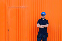 Positive Confident Adult Male Workman In Blue Protective Hardhat And Eyeglasses Smiling Friendly While Standing Against Bright Orange Wall Of Workshop