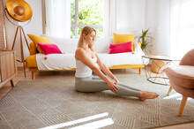Sporty Young Slim Female In Activewear Stretching Arms And Shoulders After Fitness Workout In Cozy Living Room