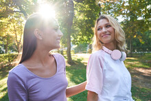 Happy Young Blond Female With Headphones On Neck Chatting With Ethnic Girlfriend While Spending Sunny Summer Day Together And Strolling In Green Park