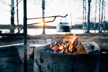 Cozy Campfire With Bright Flame Heating Metal Pot In Woods In Winter At Sunset