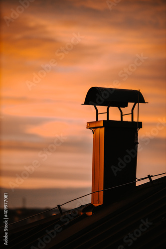 Fotografiet Vertical shot of the chimney of a house captured during the colorful sunset