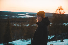Side View Of Calm Female Adventurer In Warm Outerwear Standing On Hill In Evergreen Woods And Looking At Camera On Background Of Vivid Orange Sundown