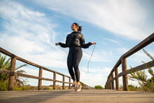 From Below Full Body Of Fit Sporty Female In Black Sportive Outfit Jumping With Skipping Rope On Wooden Walkway During Outdoor Fitness Training In Summer Day