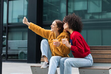Content Multiracial Female Best Friends With Takeaway Juice Cuddling On Bench On Street And Taking Selfie On Smartphone At Weekend