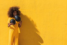 Happy African American Teen Girl With Curly Hairstyle Holding Black Balloon While Standing Against Yellow Background