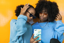 Young African American Women In Stylish Sunglasses And Lilac Clothes Taking Selfie On Mobile Phone Against Yellow Background