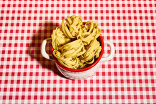 From Above Of Delicious Uncooked Fettuccine Pasta Nests Placed In Saucepan On Checkered Tablecloth In Kitchen