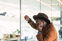 Self Esteem Young Bearded Ethnic Guy In Fashionable Sunglasses And Hat Leaning On Glass Wall Of Modern Building And Listening To Music In TWS Earphones