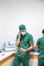 Male Dentist In Mask And Uniform Speaking On Smartphone While Holding Dental Cast In Modern Dental Hospital