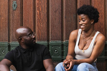 Amazed Young African American Female Reacting On News From Boyfriend While Sitting Together Against Wooden Wall