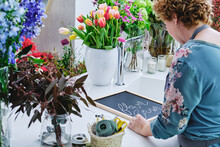 Side View Of Unrecognizable Female Florist Writing On Black Chalkboard Preparing Bright Flower Shop For Christmas Holidays